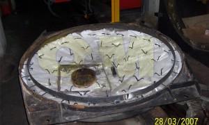 Πόρτα λέβητα νερού ισχύος 2.600.000 Kcal/h, σε διαδικασία προετοιμασίας νέας χύτευσης πυρίμαχου υλικού. Διακρίνονται η στεφάνη συγκράτησης του πυροχώματος, η κεραμική κουβέρτα μείωσης της θερμικής αγωγιμότητας, τα άγκιστρα τύπου V συγκράτησης του πυροχώματος και το νάυλον προστασίας της κεραμικής κουβέρτας από την υγρασία.